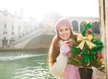 Smiling woman with Christmas tree near Rialto Bridge in Venice Stock Photo