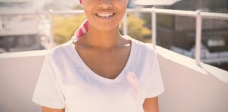 Smiling woman in the city with breast cancer awareness stock photography