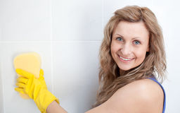 Smiling woman cleaning a bathroom Royalty Free Stock Images
