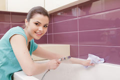 Smiling woman cleaning bathroom. Joyful work. Youthful lady cleaning bathroom with help of white cloth royalty free stock photos