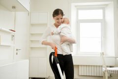 Smiling woman cleaning the carpet holding a baby Stock Photos
