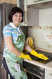 Smiling woman cleaning  cooker Royalty Free Stock Photography