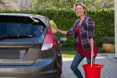 Smiling woman cleaning her car with sponge stock photo