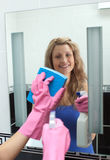 Smiling woman cleaning a mirror in a bathroom. At home royalty free stock photography
