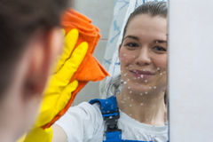 Smiling woman cleaning mirror with rag Royalty Free Stock Photography