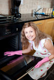 Smiling woman cleaning the oven Stock Photography