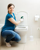 Smiling  woman cleaning toilet seat Stock Photo