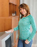 Smiling woman cleaning TV Stock Photography