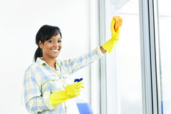 Smiling woman cleaning windows Royalty Free Stock Image