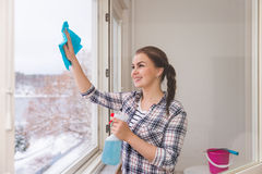 Smiling woman cleaning windows Royalty Free Stock Images