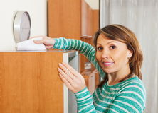 Smiling woman cleaning wooden furiture Stock Photography