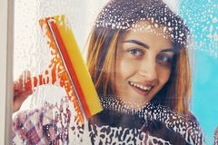 Woman cleans the window with a brush Royalty Free Stock Photography