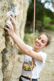 Smiling woman climber is preparing to scale the rock Stock Photo