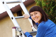 Smiling woman climbing on aluminum ladder in garden Royalty Free Stock Images