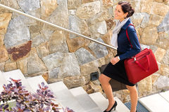 Smiling woman climbing stairs luggage traveling arriving Royalty Free Stock Photography
