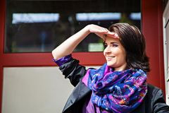 Smiling woman in cloak and colored scarf Royalty Free Stock Photos