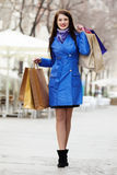 Smiling woman in  cloak with purchases Stock Photo
