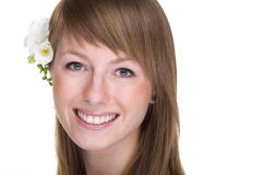 Smiling woman closeup. Closeup of the face of a smiling young woman with flowers in her hair, isolated against a white background Stock Photo