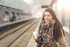 Smiling woman in coat with coffee at station Stock Images
