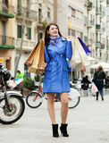 Smiling woman in coat with purchases Stock Images