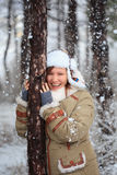 Smiling woman in coat with white fur, hat with ear flaps and gre. Young beautiful smiling woman in coat with white fur, hat with ear flaps and grey fingerless Royalty Free Stock Photography