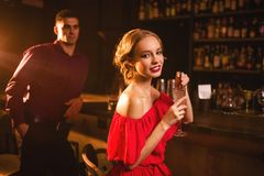Smiling woman with cocktail in hand, flirting. Smiling women in red dress with cocktail in hand, men behind bar counter, flirting. Date in nightclub, attractive Stock Photos
