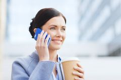 Smiling woman with coffee calling on smartphone Royalty Free Stock Images