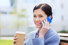 Smiling woman with coffee calling on smartphone Stock Photography