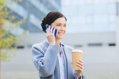 Smiling woman with coffee calling on smartphone Royalty Free Stock Image