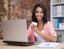 Smiling woman with coffee cup and laptop sitting at her desk Stock Photography