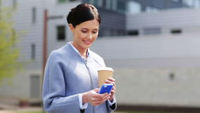 Smiling woman with coffee cup and smartphone stock video footage