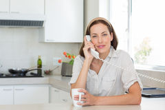 Smiling woman with coffee cup using landline phone in kitchen Stock Images