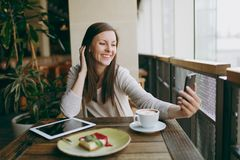 Smiling woman in coffee shop with cup of cappuccino, cake, doing selfie on mobile phone, relaxing in restaurant during royalty free stock photo