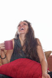 Smiling woman with coffee on sofa stock photo