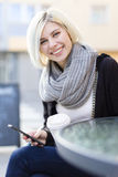 Smiling woman with coffee and using phone outdoor Stock Image