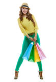Smiling woman with colorful shopping bags on white background. Colourful shopping vibes. Full length portrait of smiling brunette woman in hat and bright clothes Stock Images