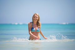 Smiling woman coming out of water Royalty Free Stock Image
