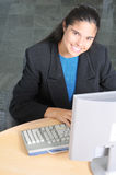 Smiling Woman at Computer in Office Stock Photography