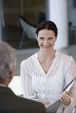 Smiling woman consultant. Woman consultant sitting in front of a client Royalty Free Stock Photo