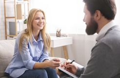 Smiling woman during consultation with life coach. Success of life coaching. Smiling women talking to professional psychological consultant, talking about her royalty free stock photos