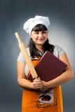 Smiling woman cook. Holding rolling-pin and book with recipes Royalty Free Stock Photo
