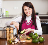 Smiling woman cooking with avocado. In home kitchen Stock Photos