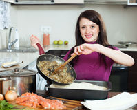 Smiling  woman cooking fish pie Royalty Free Stock Images
