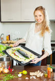 Smiling woman cooking fish in sheet pan Stock Image