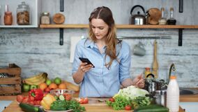 Smiling woman cooking food check vegetables look at smartphone. Shot on RED Raven 4k Cinema Camera