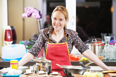 Smiling woman cooking in her kitchen Royalty Free Stock Photo