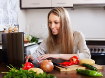 Smiling woman cooking with laptop Stock Photography
