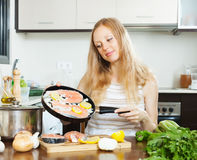 Smiling woman cooking salmon fish Stock Images
