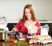 Smiling woman cooking scrambled eggs in home Royalty Free Stock Photos