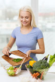 Smiling woman cooking vegetable salad at home Royalty Free Stock Images